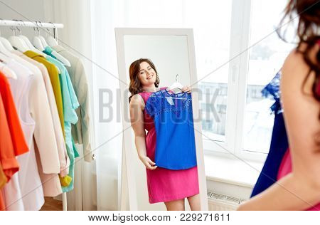 clothing, fashion and people concept - happy plus size woman in pink dress with blue top looking at mirror at home