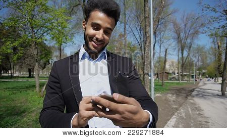 Charming Man Talking With Lady And Gets To Use Phone.female Hand With Pink Nail Varnish Clicks On Sc