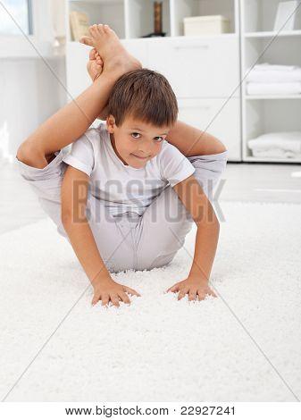 Little contortionist boy bending himself in his room
