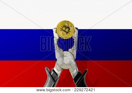 Bitcoin Coin Being Squeezed In Vice On The Russian Flag Background; Concept Of Cryptocurrency Bitcoi