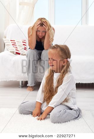 Little girl having a temper tantrum with her desperate mother in background