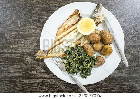 Barbecued Sea Bass Served With Lemon, Baked Potatoes And Spinach On White Plate
