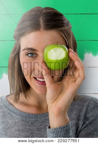 Digital composite of Woman against wood with apple over eye