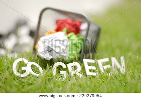Closeup Blurred Image Concept. Used Color Paper In Thrash Can With Alphabet Go Green On Green Grass