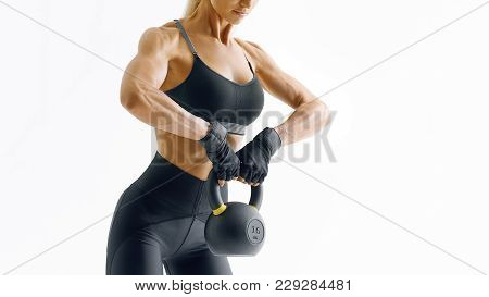 Closeup Photo Of Attractive Female Athlete Exercising With Kettlebell For Muscle And Strength Buildi
