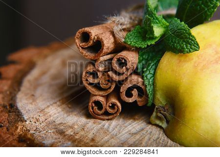 Cinnamon Sticks Tied And Cut Apple, Green Fresh Mint On Wooden Background. Selective Focus.