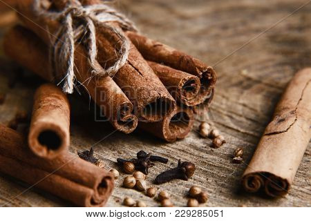 Cinnamon Sticks On Wood Table With Bundles Of Cinnamon, Coriander, Cloves, In Soft Focus In Wooden B