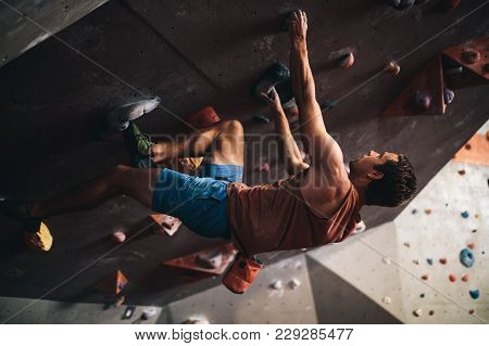 Man Bouldering At An Indoor Climbing Centre While A Woman Looks On. Climber Practicing Rock Climbing