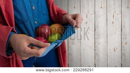 Digital composite of Person holding apples in jumper against wood