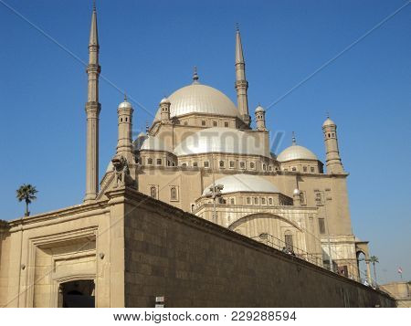 Muslim Mosque With Minaret On Blue Sky Background. Beautiful Mosque Of Sandy Color With Against Blue