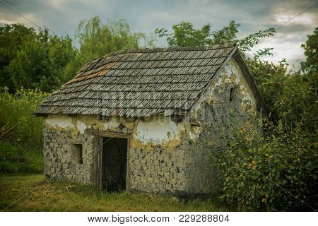 Decay, decline, ruins. Village with abandoned building. House barrack in yard on natural landscape. Rural lifestyle, countryside. Architecture, structure, construction. poster