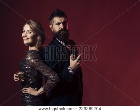 Man And Woman In Fancy Clothes Drink Wiskey On Burgundy Background, Copy Space. Corporate Party Conc