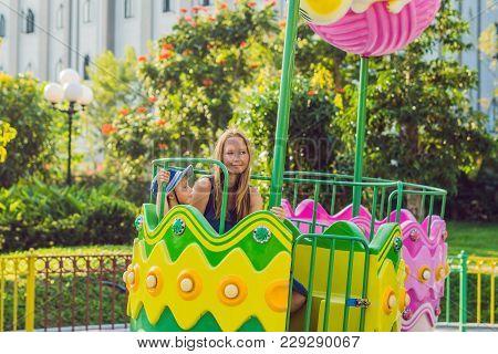 Mom And Son Having Fun At An Amusement Park.