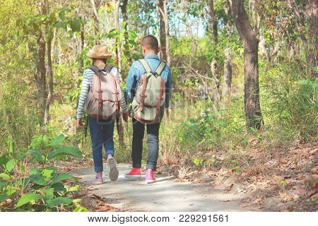 Asia ,young Backpacker With Backpack Traveling Alone Forest,walking Along The Road Stretch, Relax Ti
