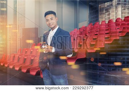 Young Asian Businessman In A Modern Cinema Interior Corner With Gray And Wooden Walls, A Concrete Fl