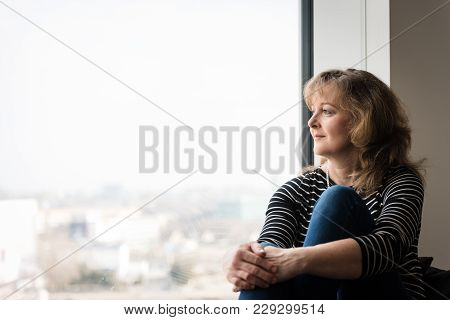 Smiling Woman Enjoying The View Outside Through Window