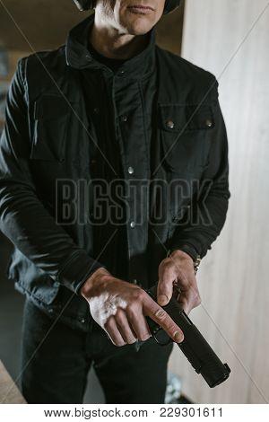 Cropped Image Of Man Preparing To Shoot In Shooting Range