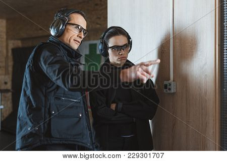 Instructor Pointing On Something In Shooting Gallery