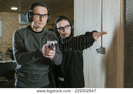 Female Instructor Showing Where Shoot To Client In Shooting Range