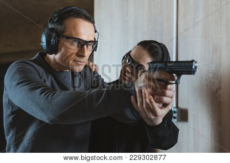 Female Instructor Describing Client How To Shoot In Shooting Range