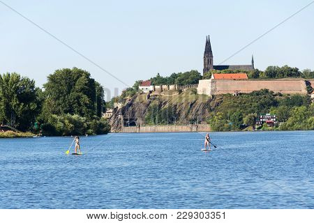 Prague, Czech Republic - August 19 2012: Woman Sailing On Standup Paddleboard On Vltava River With V
