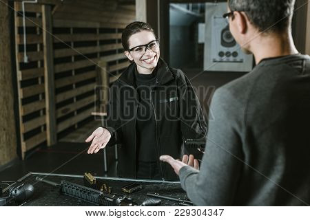 Smiling Customer Talking With Shooting Instructor In Shooting Range