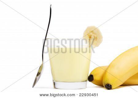 banana milkshake with a piece of banana a spoon and bananas aside