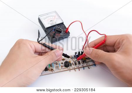 Technician Hand With Multimeter Probes Repairing Circuit Board