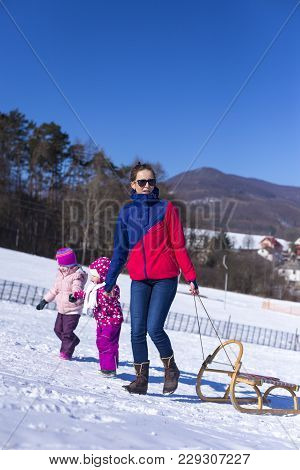 Outdoor Fun For Family Christmas Vacation. In A Beautiful Sunny Winter Day, Mummy Is Sledging With H