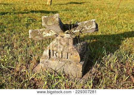 R.i.p. Rest In Peace Inscribed In An Old Grave Marker With A Cross Which Has Crumbled.