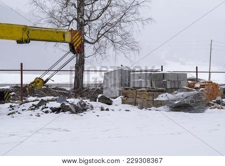 Building Materials In The Snow And The Crane Jib On The Road