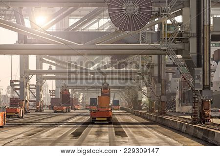 Automated Guided Vehicles Moving Shipping Containers To And From Gantry Cranes In A Port Container T
