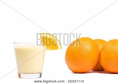 piece of a orange on a orange milkshake in front of oranges