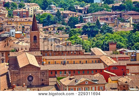 Bologna, Italy. Top view to old town with terracotta houses and tegular roofs. High tower of temple with broach. Green trees. Scenic landscape of sunny hot italian summer day.