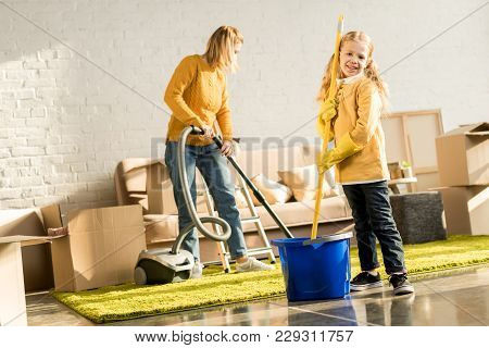 Mother And Daughter With Mop And Vacuum Cleaner Cleaning Room After Relocation