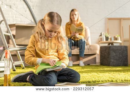 Child Cleaning Photo Frames While Mother Reading Book On Sofa During Relocation
