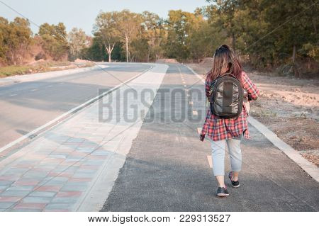 Travel Concept. Traveling Woman With Backpack Walking On Asphalt Road Countryside