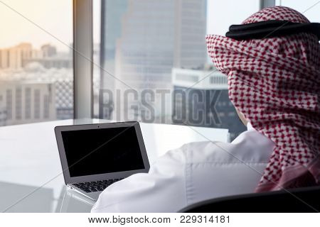Saudi Arab Man Watching Laptop At Work Contemplating