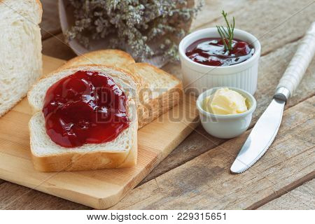 Delicious Toast Bread Served With Butter And Spread With Strawberry Jam. Sliced Bread On Wood Cuttin
