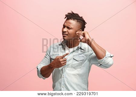 Sore Ear. Ear Ache Concept. The Sad Afro Man With Ear Ache Or Pain On Trendy Pink Studio Background.