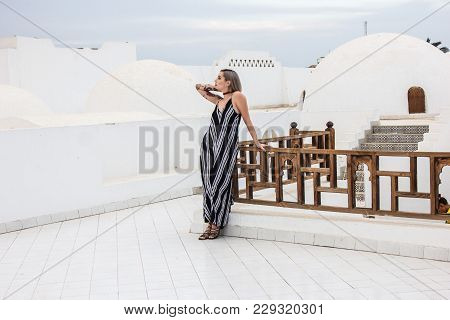 Beautiful Girl In Dress Looking Away While Leaning At Wooden Railing At Resort In Egypt