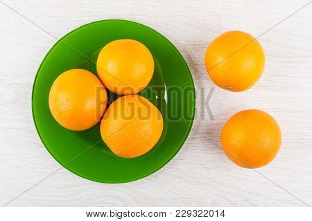 Ripe Oranges In Green Plate And On Wooden Table. Top View