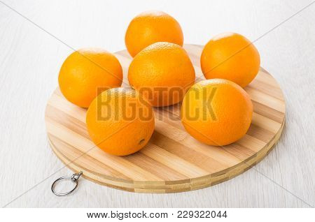 Ripe Oranges On Round Striped Cutting Board On Wooden Table