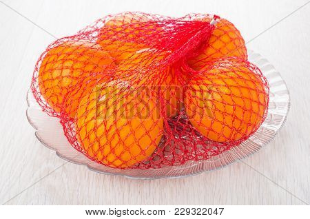 Ripe Oranges In Red Mesh On Transparent Dish On Wooden Table