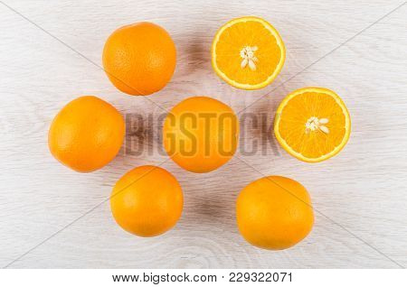 Whole Oranges And Halves Of Orange On Wooden Table. Top View