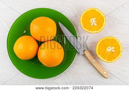 Whole Oranges In Green Plate, Knife And Halves Of Orange On Wooden Table. Top View