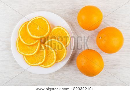 Slices Of Orange In White Plate And Whole Oranges On Wooden Table. Top View