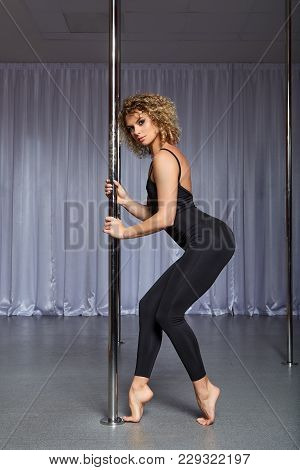 Beautiful Blond Young Woman Training On Pylon At Pole Dance Studio. Copy Space.