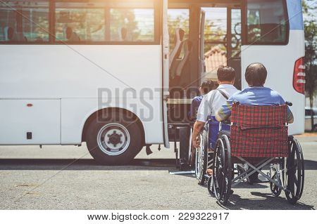 Disabled People Sitting On Wheelchair And Going To The Public Bus