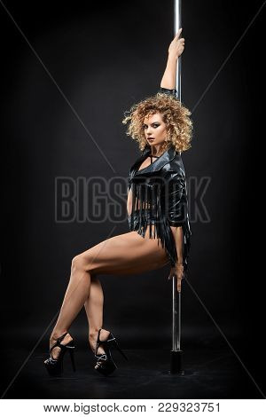 Beautiful Young Woman Pole Dancer In Leather Jacket And Bodywear On Pylon. Studio Shot On Black Back